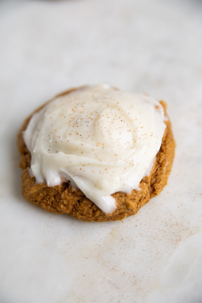 one cookie with cinnamon sprinkled on top of cream cheese frosting.