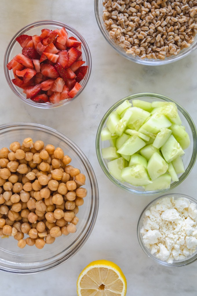separate bowls of farro, cucumber, strawberries and chickpeas.