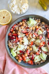 Farro salad with strawberries and cucumbers in a bowl with a spoon.