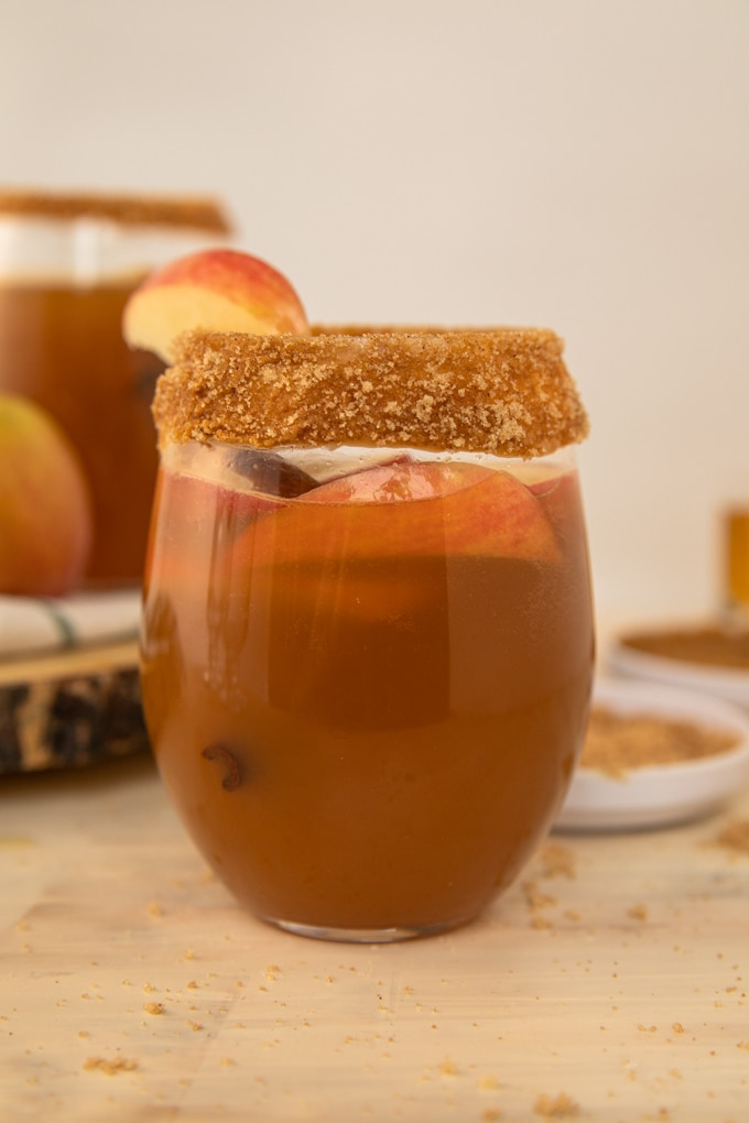 a glass full of apple cider, apples and a cinnamon stick.