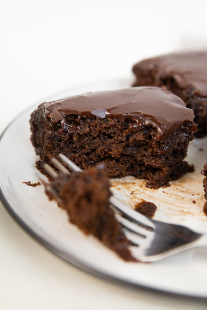 a fork taking a piece of brownie with frosting on top.