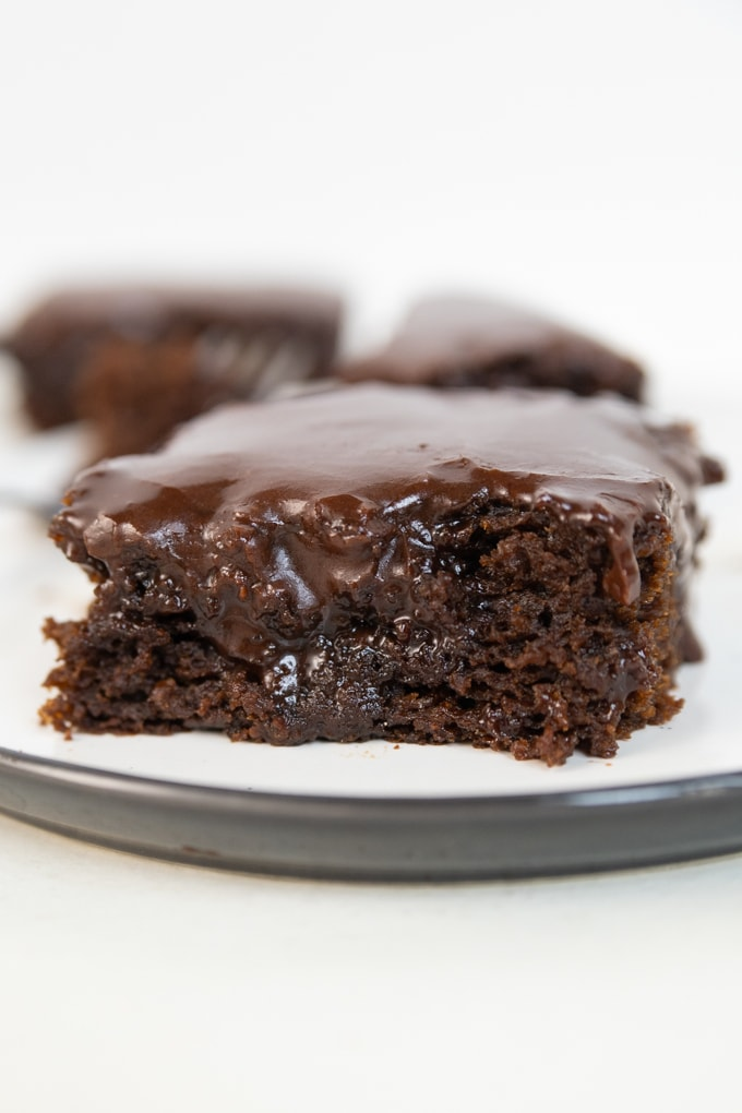 a chocolate brownie on a plate with frosting on top.