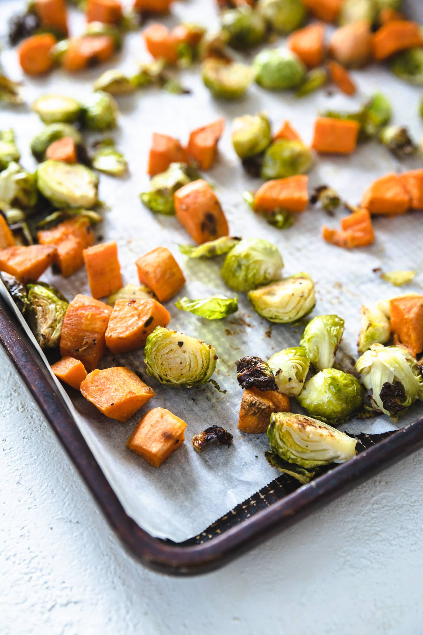 A baking sheet lined with parchment paper with sweet potatoes and brussel sprouts on it.