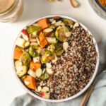 A buddha bowl filled with fall vegetables and quinoa.