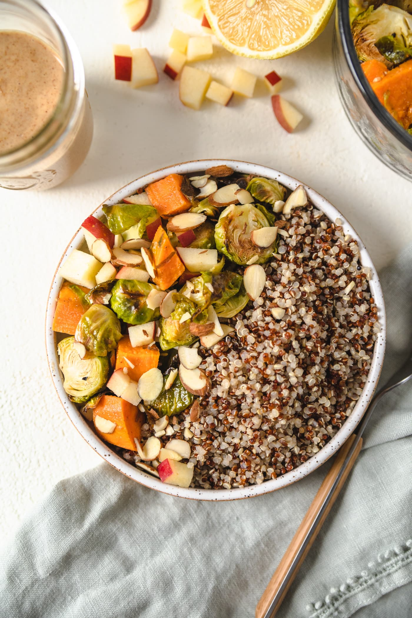 A buddha bowl filled with fall vegetables, quinoa next to a jar of almond ginger dressing.