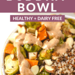 fall almond buddha bowl with dressing over top a bed of vegetables and quinoa.