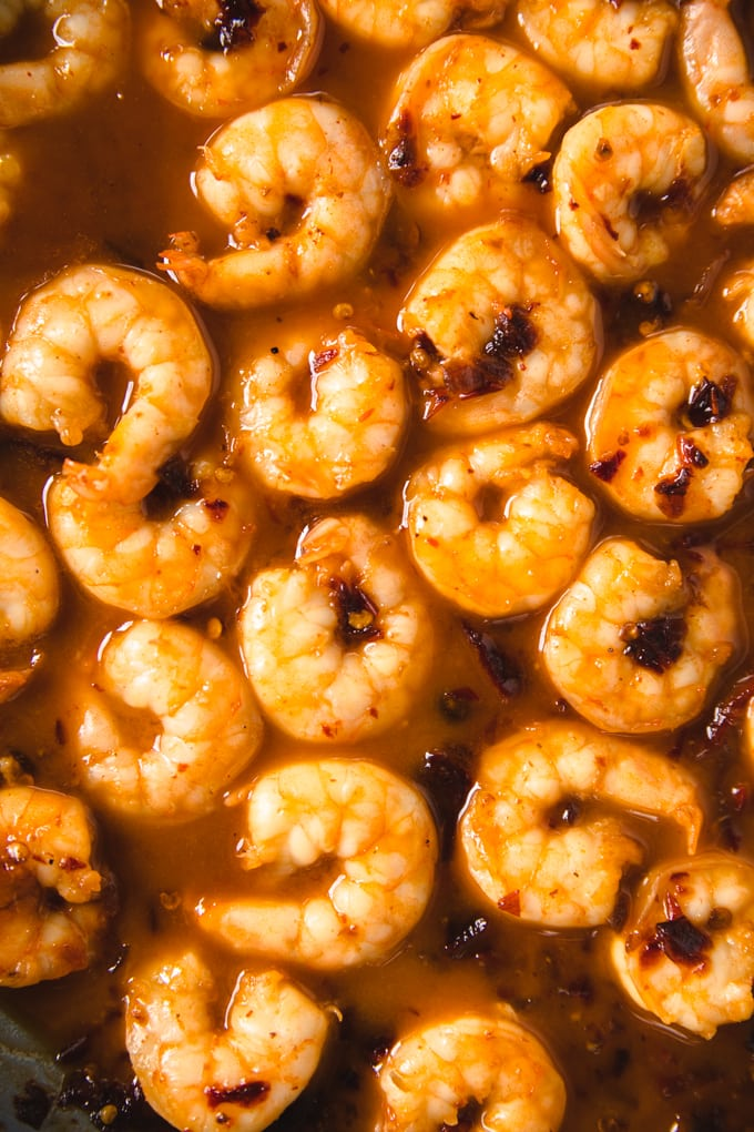 shrimp in a skillet with sauce.
