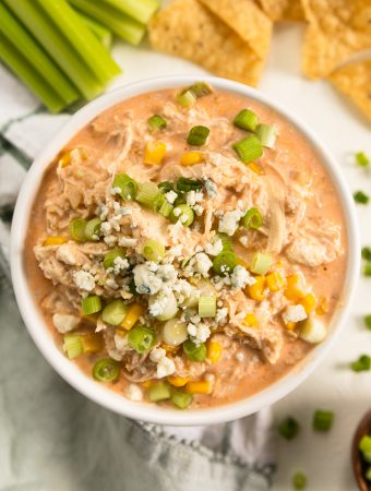 a bowl of buffalo chicken dip with corn and blue cheese on top.