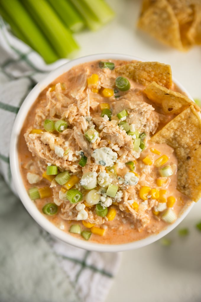 blue cheese, corn and tortilla chips in a bowl of buffalo chicken dip.