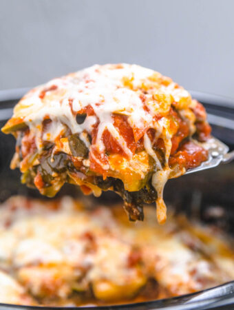 a slice of vegetarian lasagna being lifted from a slow cooker with a spatula.