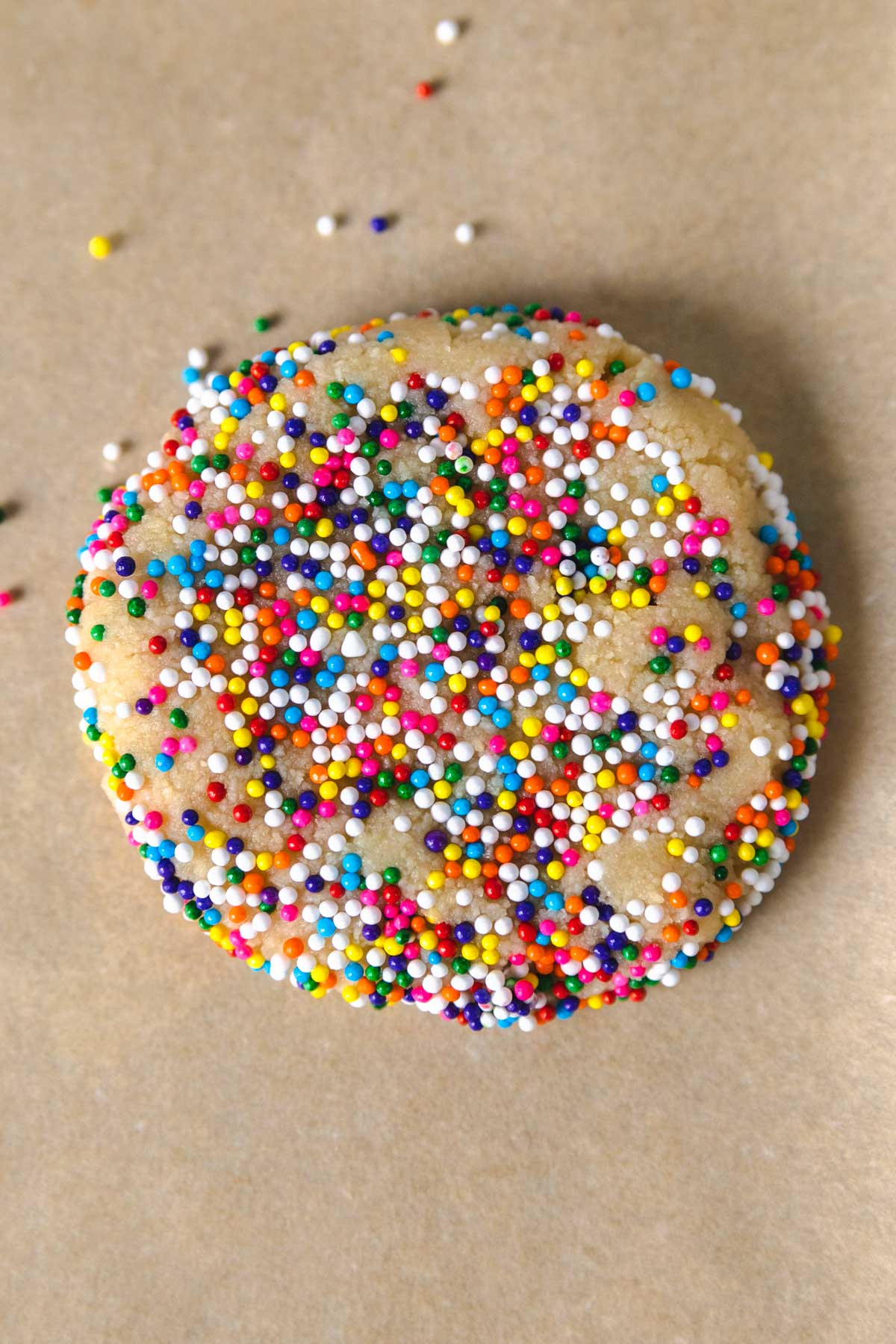 a cookie with sprinkles pressed around the sides and edges on a sheet pan.