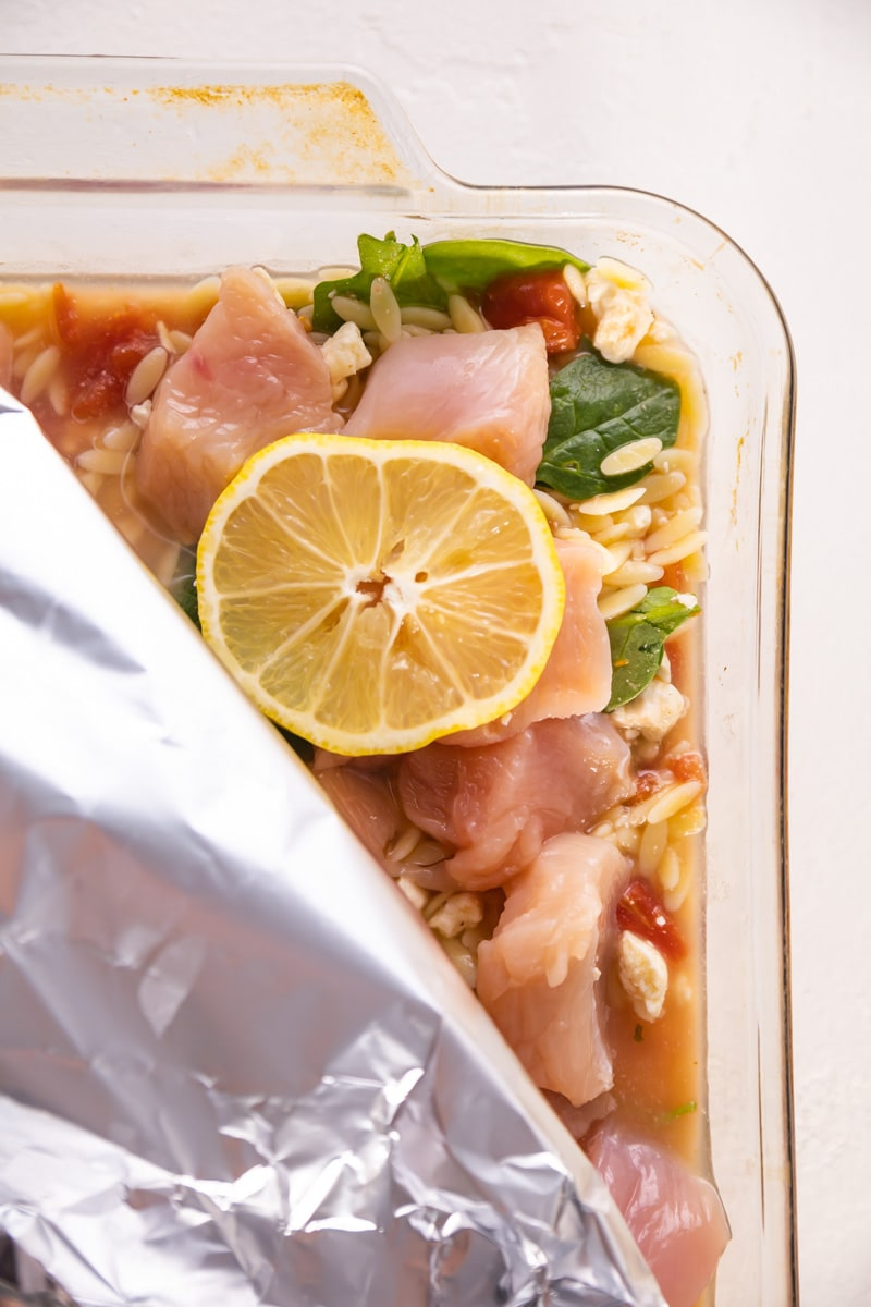 raw chicken on top of the casserole with foil and lemon on top ready to be baked in the oven.