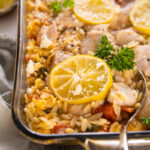 a casserole dish with a spoon serving lemon and chicken.