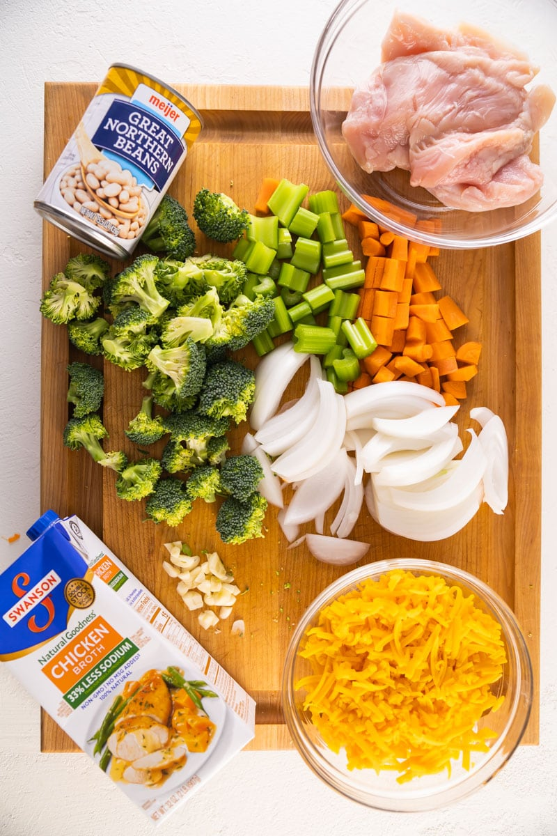 ingredients for chicken broccoli cheddar soup on a cutting board spaced out.
