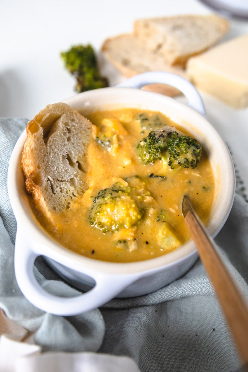 a bowl of broccoli cheddar soup with chicken with a spoon coming out of the side.
