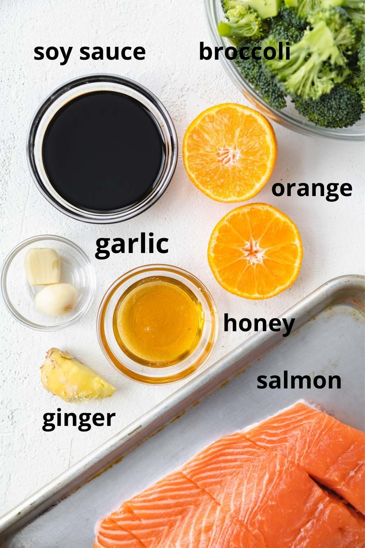 labeled ingredients for this ginger orange salmon sheet pan dinner in separate bowls.
