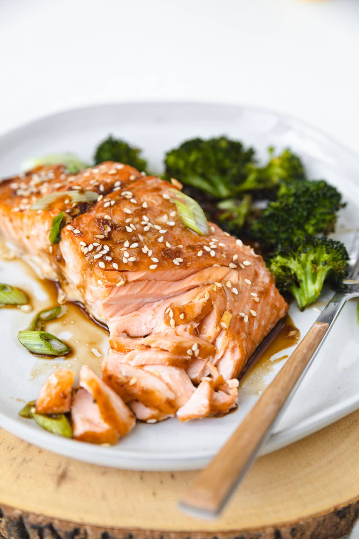 salmon topped with sesame seeds and flaked with a fork.On a plate with broccoli.