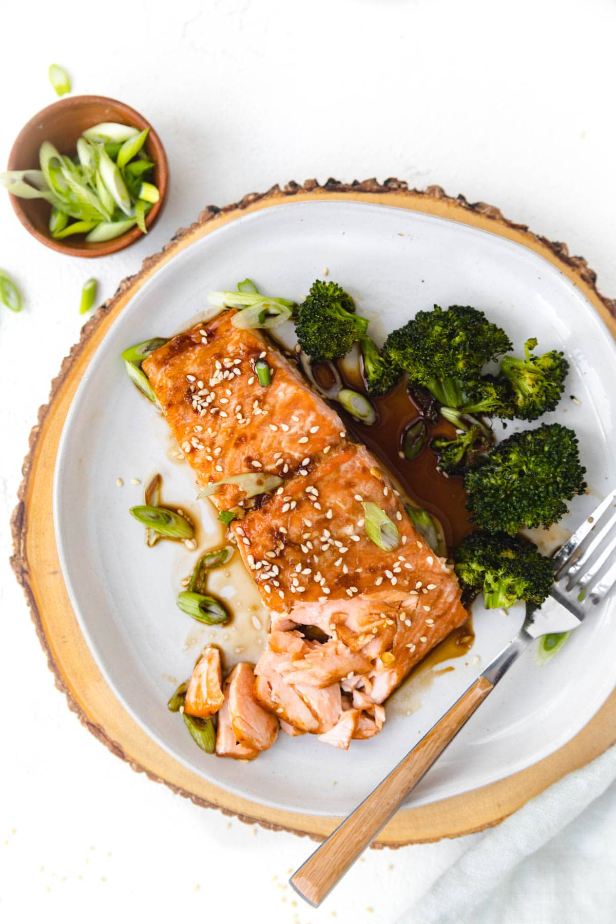 salmon on a plate with broccoli and fork. Sauce dripping off the salmon onto the plate.