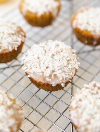 Lemon coconut muffin on a cooling rack with shredded coconut on top.