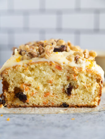 carrot cake bread sliced in half with frosting and walnuts on top.