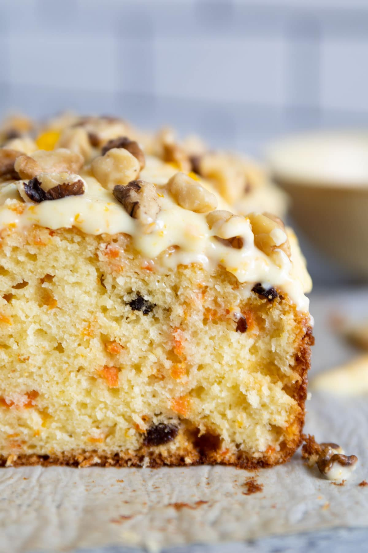 up close shot of frosting on the bread with walnuts on top. Carrot and raisins are inside the bread.