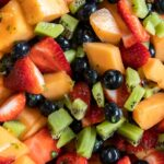 Assorted mixed fruit salad in a bowl with dressing.